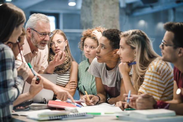 mature teacher teaching group of college students at campus. - professor stock pictures, royalty-free photos & images