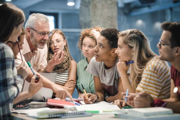 mature teacher teaching group of college students at campus. - professore foto e immagini stock