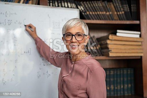 istock Mature teacher writing on whiteboard 1201405255