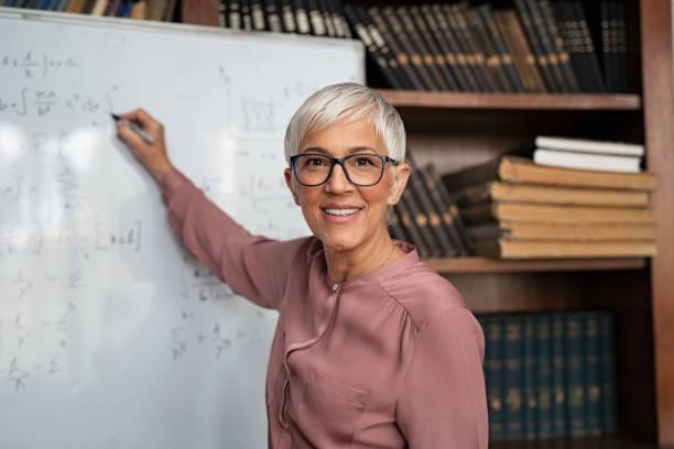 Reife Lehrer schreiben auf Whiteboard – Foto