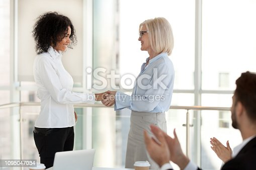 924520168 istock photo Mature team leader congratulating happy successful african worker with promotion 1095047034