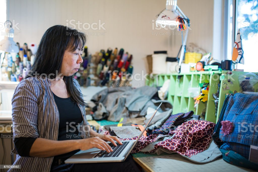 A mature textile entrepreneur working on a laptop computer in her studio stock photo