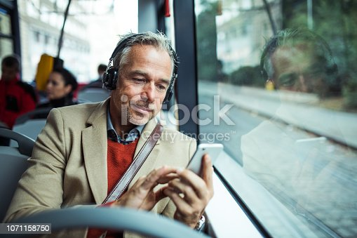 istock Mature tired businessman with heaphones and smartphone travelling by bus in city. 1071158750