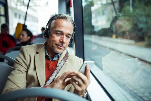 volwassen moe zakenman met heaphones en smartphone reizen per bus in de stad. - forens stockfoto's en -beelden