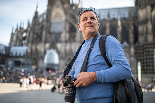 Mature tourist holding camera and looking around while standing in front of Cologne Cathedral