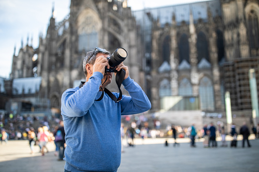 Mature tourist photographing while standing in front of Cologne Cathedral