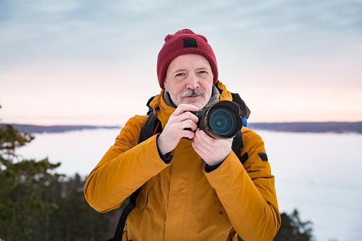 Mature traveler with camera exploring Finland