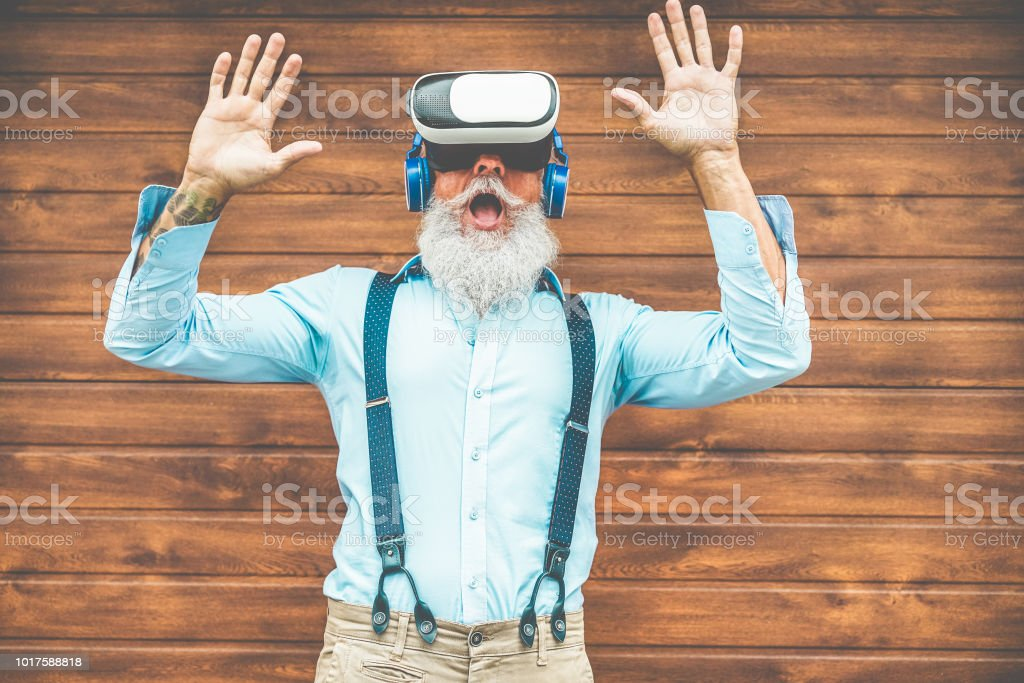 bc8a6b7786 Mature trendy man having fun with virtual reality goggles technology -  Senior fashion guy wearing vr headset - Tech
