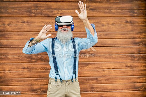 istock Mature trendy man having fun with virtual reality goggles technology - Senior fashion guy wearing vr headset - Tech, modern lifestyle and joyful elderly lifestyle concept - Focus on face, 3d glasses 1144989257
