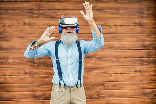 Mature trendy man having fun with virtual reality goggles technology - Senior fashion guy wearing vr headset - Tech, modern lifestyle and joyful elderly lifestyle concept - Focus on face, 3d glasses