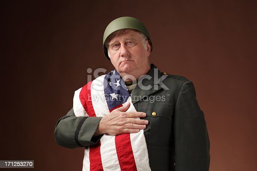 mature US soldier with stars and stripes, hand on hearts on plain background