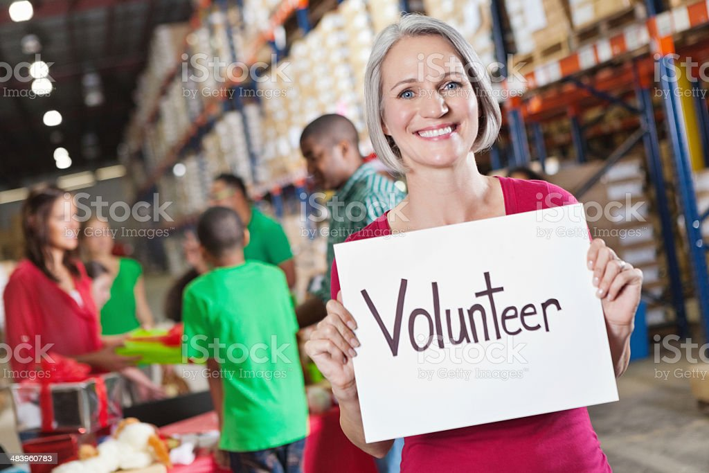 Mature volunteer at charity toy food donation drive with sign royalty-free stock photo