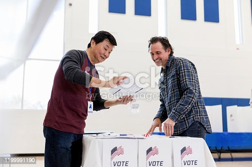 The mature male volunteer helps the mature man sign up to vote by reviewing the information with him.