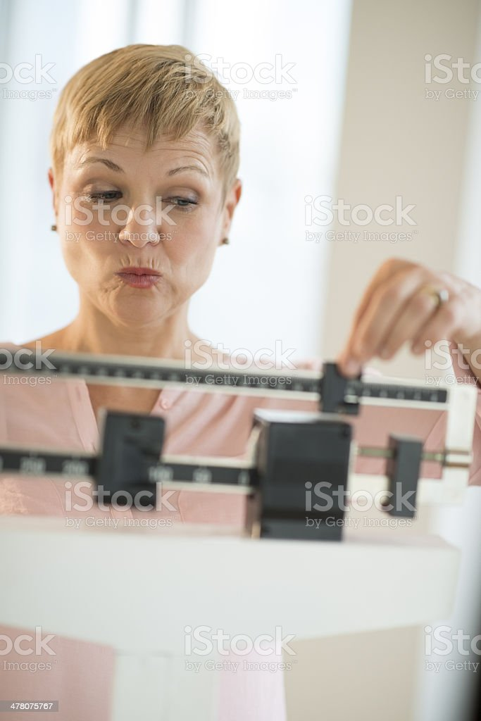 Mature Woman Adjusting Sliding Weight Scale stock photo