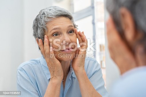 Beautiful senior woman checking her face skin and looking for blemishes. Portrait of mature woman massaging her face while checking wrinkled eyes in the mirror. Wrinkled lady with grey hair checking wrinkles around eyes, aging process.