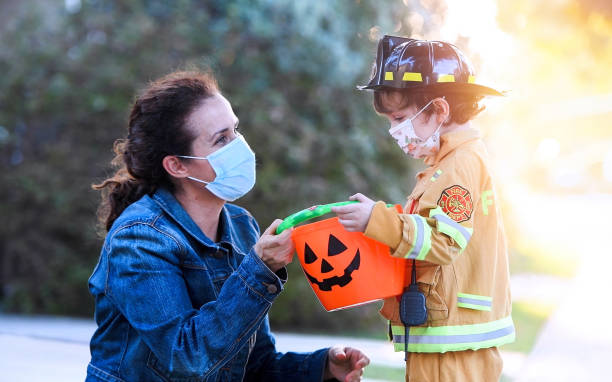 Mature woman and a child boy wearing protective face masks before going to ask trick or treat halloween Caucasian Mature woman and a child boy wearing protective face masks before going to ask trick or treat halloween halloween covid stock pictures, royalty-free photos & images