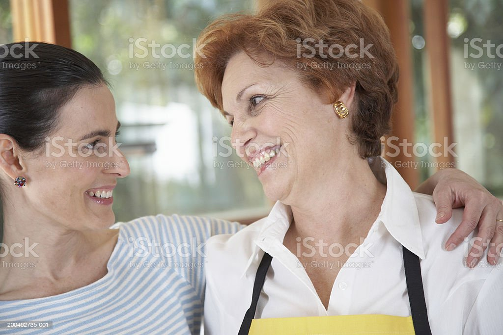 Mature woman and adult daughter smiling at each other in kitchen royalty-free stock photo