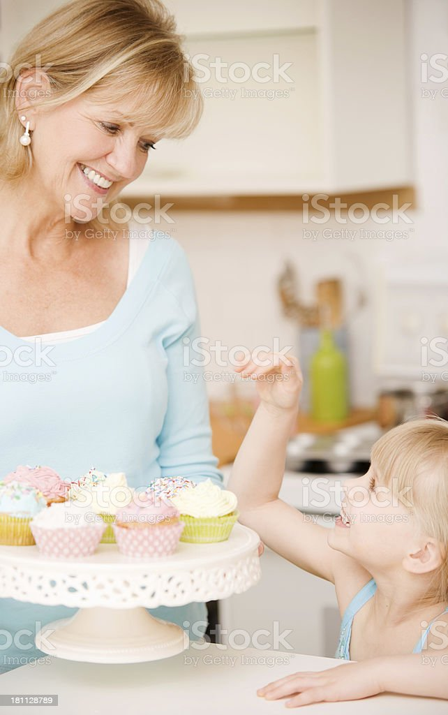 Mature Woman and Child Eating Cupcakes royalty-free stock photo