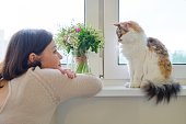 Mature woman and domestic tricolor cat sitting on the window, owner watching and talking with pet