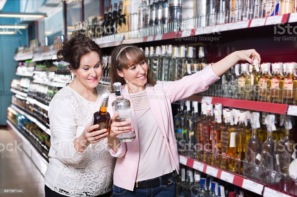 Mature woman and her daughter buying strong alcohol foto