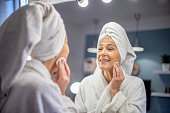 Portrait of beautiful senior Caucasian woman in towel looking herself in the mirror and cleaning face. She is going through morning beauty routine in bathroom. Skin Care and Hygiene