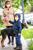 Caucasian Mature woman and her son walking their  doberman pet wearing a protective mask, the child is holding a US flag