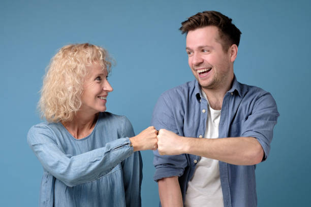 mature woman and man friends couple give bump looking at camera as partnership stock photo