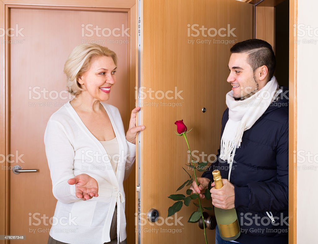 Mature woman and young guy at doorway stock photo