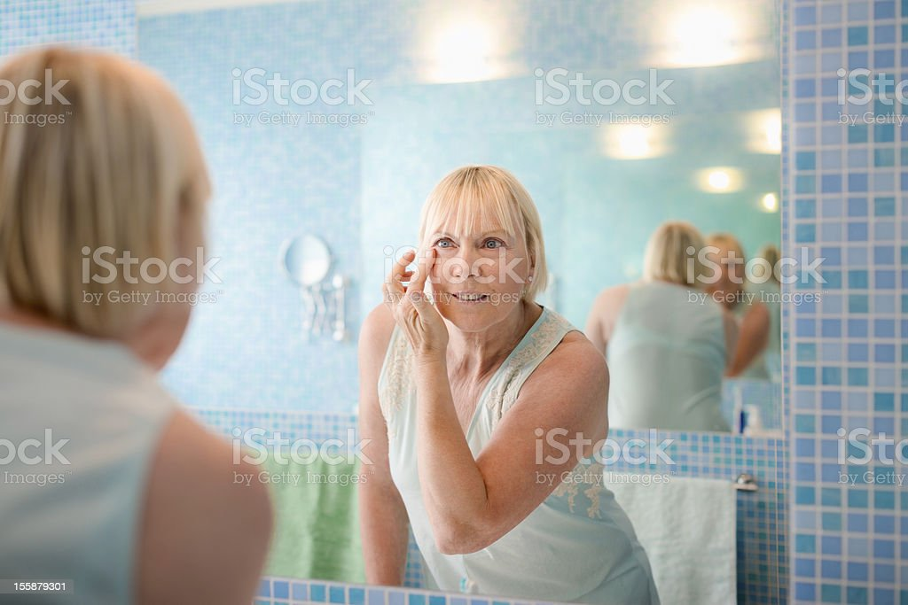 A mature woman applies face cream while looking in mirror stock photo