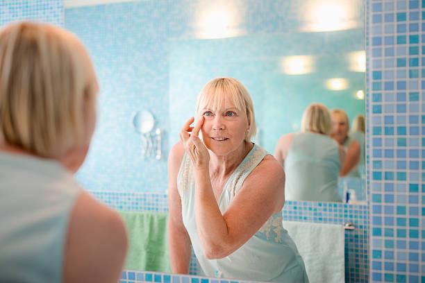 weibliche schönheit, alte frau anwendung creme auf gesicht zu hause fühlen - alte spiegel stock-fotos und bilder