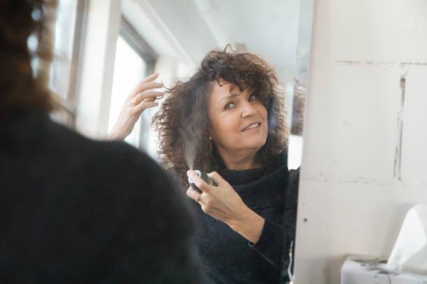 Reife Frau, die Anwendung von Haarspray vor Spiegel – Foto
