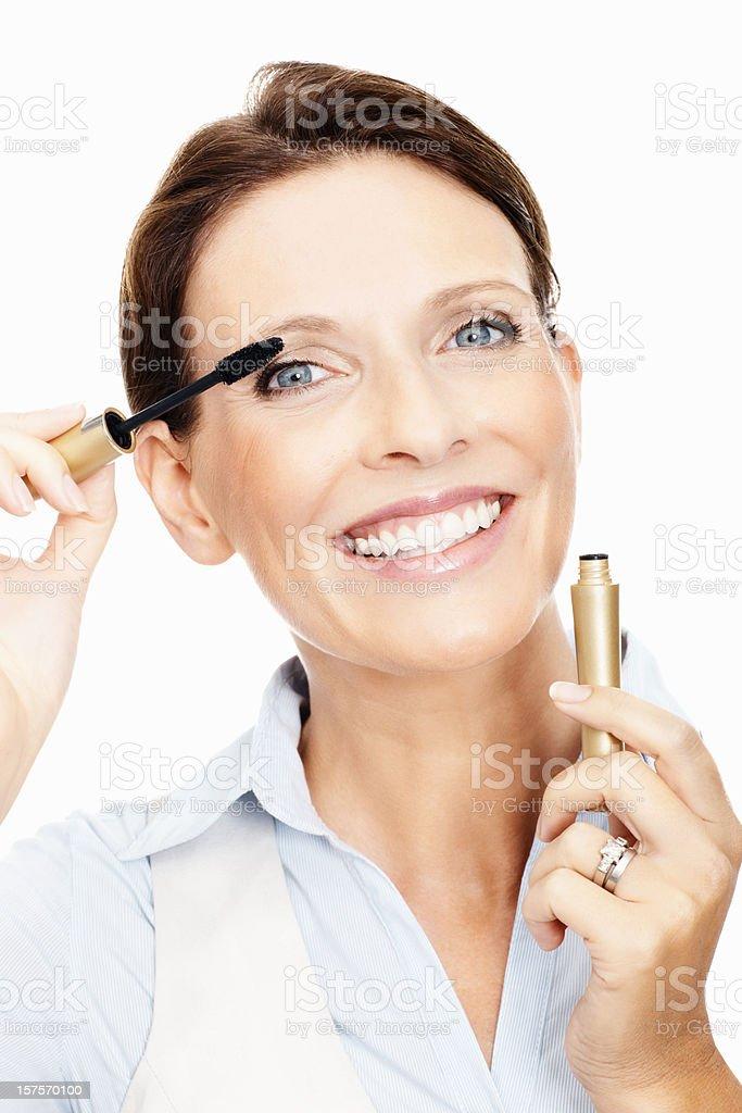 Mature woman applying mascara stock photo