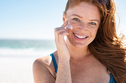 Smiling young woman applying sunscreen lotion on face at beach, with copy space. Beautiful mature woman with red hair enjoying summer at sea. Portrait of happy girl using sunblock on her delicate skin with freckles and looking at camera.