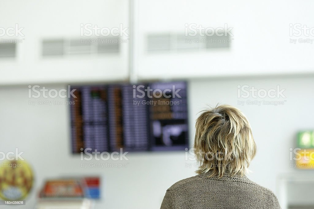 Mature woman at airport departures board royalty-free stock photo