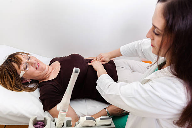 Mature Woman At Gynecologist Gynecologist Examines Mature Woman By Touching Her Abdomen. gynecological examination stock pictures, royalty-free photos & images
