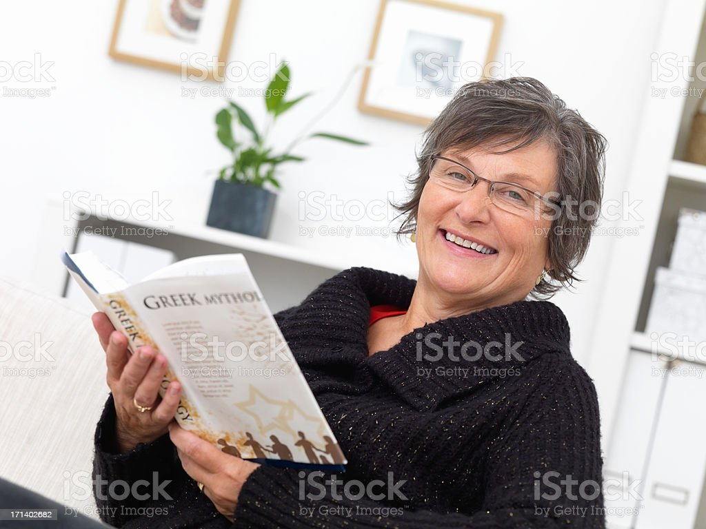 Mature woman at home reading a book  royalty-free stock photo