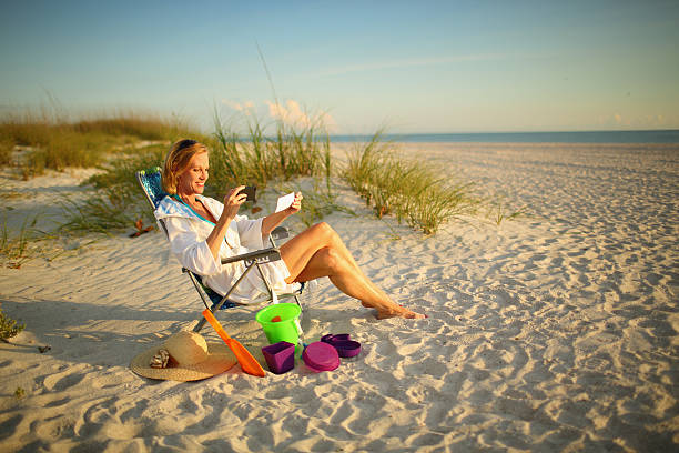 mature woman at the beach depositing a check with phone - deposit slip stock photos and pictures