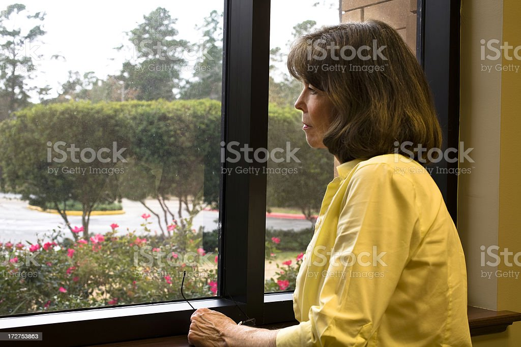 Mature woman at window royalty-free stock photo