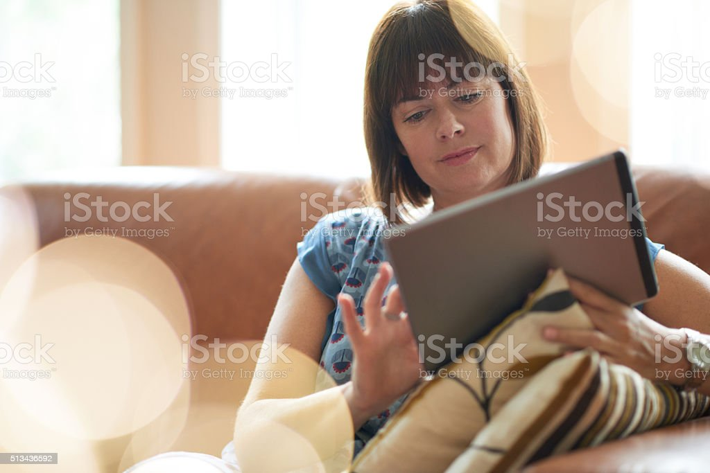 Mature woman browsing the internet on a digital tablet stock photo