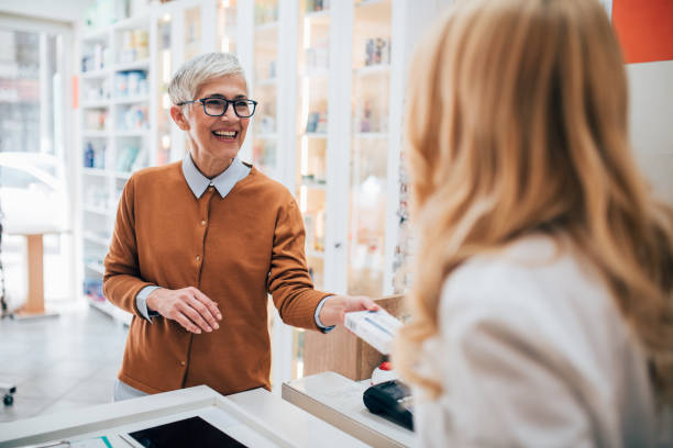 Mature woman buying a medicine at the pharmacy stock photo