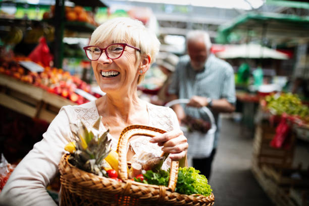 Mature woman buying vegetables at farmers market stock photo