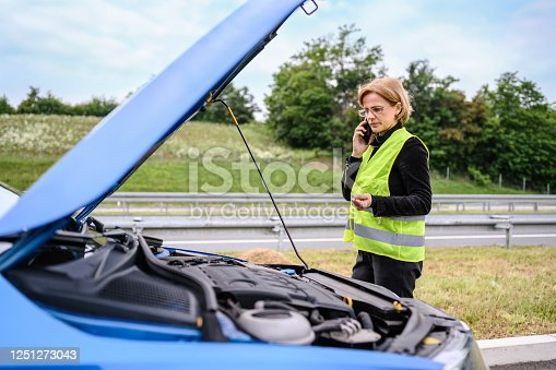 Mature woman calling the car service after a vehicle breakdown