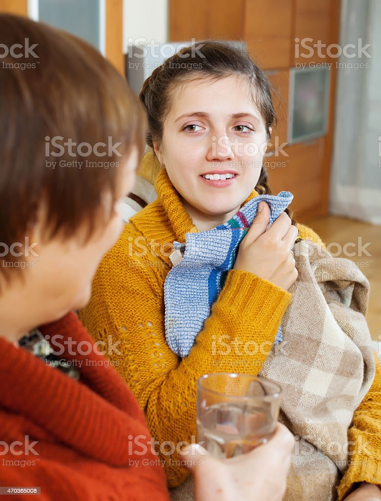 Mature woman caring for  adult daughter has cold stock photo