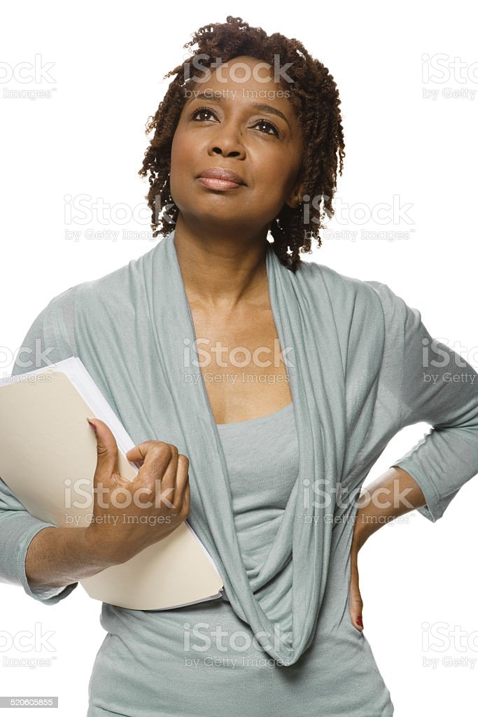 Mature woman carrying files, hand on hip, looking away stock photo
