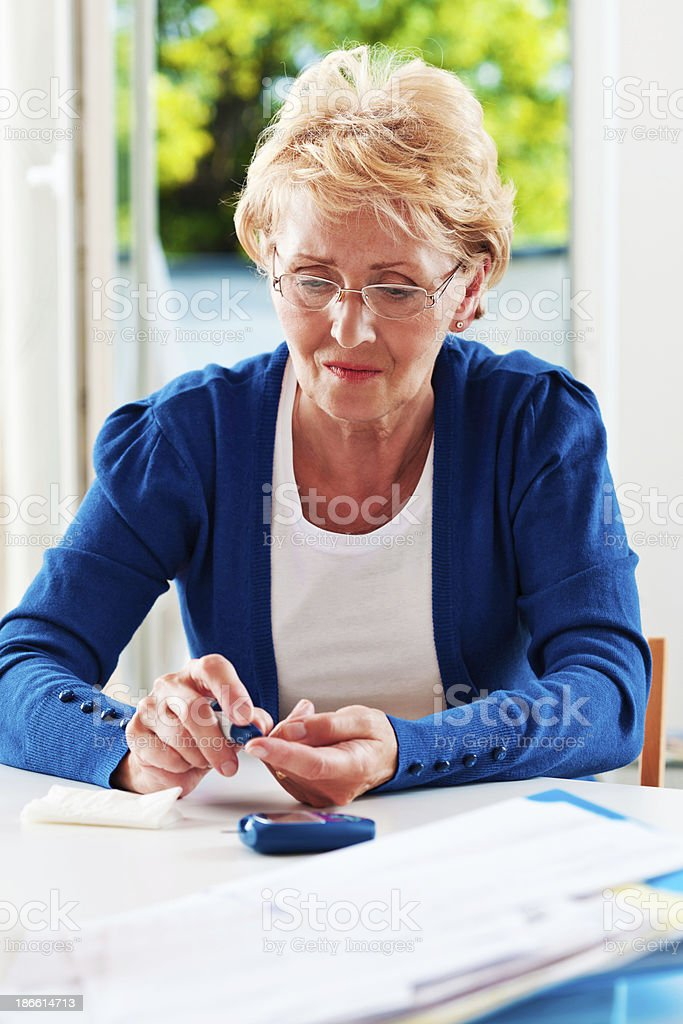 Mature woman checking glucose level stock photo