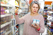 Portrait of aged woman choosing fresh dairy products on shelves in grocery shop