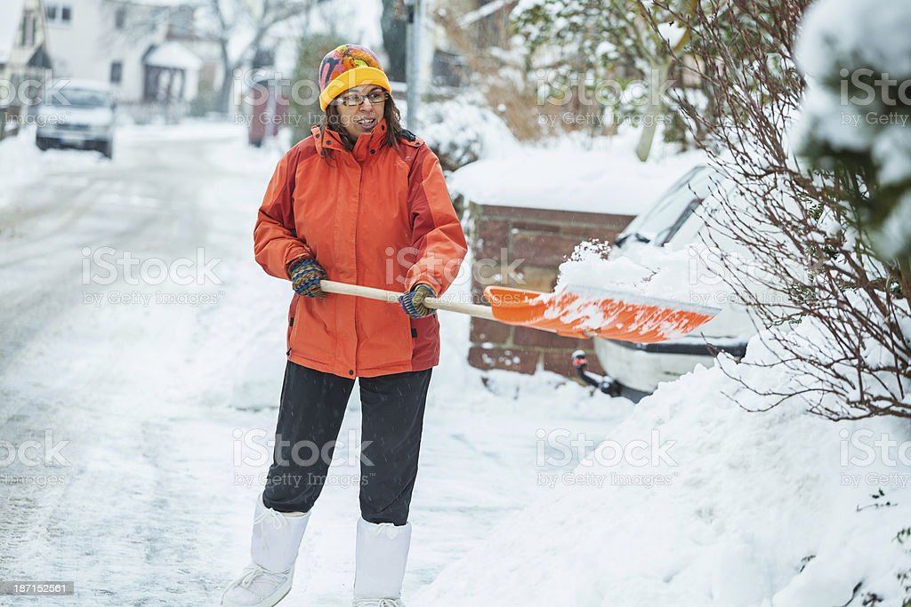Mature woman cleaning snow in front of her house stock photo