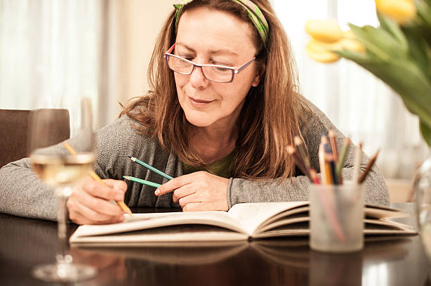Mature woman coloring and drinking white wine stock photo