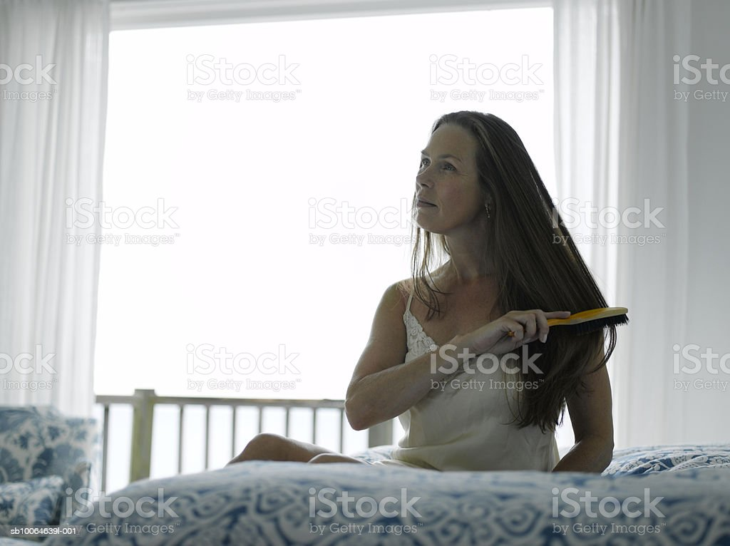 Mature woman combing hair on bed royalty-free stock photo