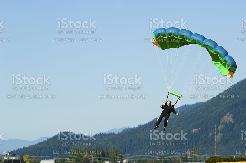 Mature woman comes in for a landing with her parachute. stock photo